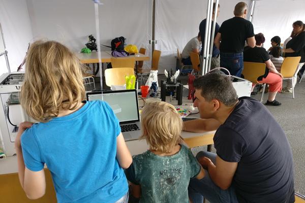 Ein Erwachsener und zwei Kinder sitzen an einem Tisch und experimentieren