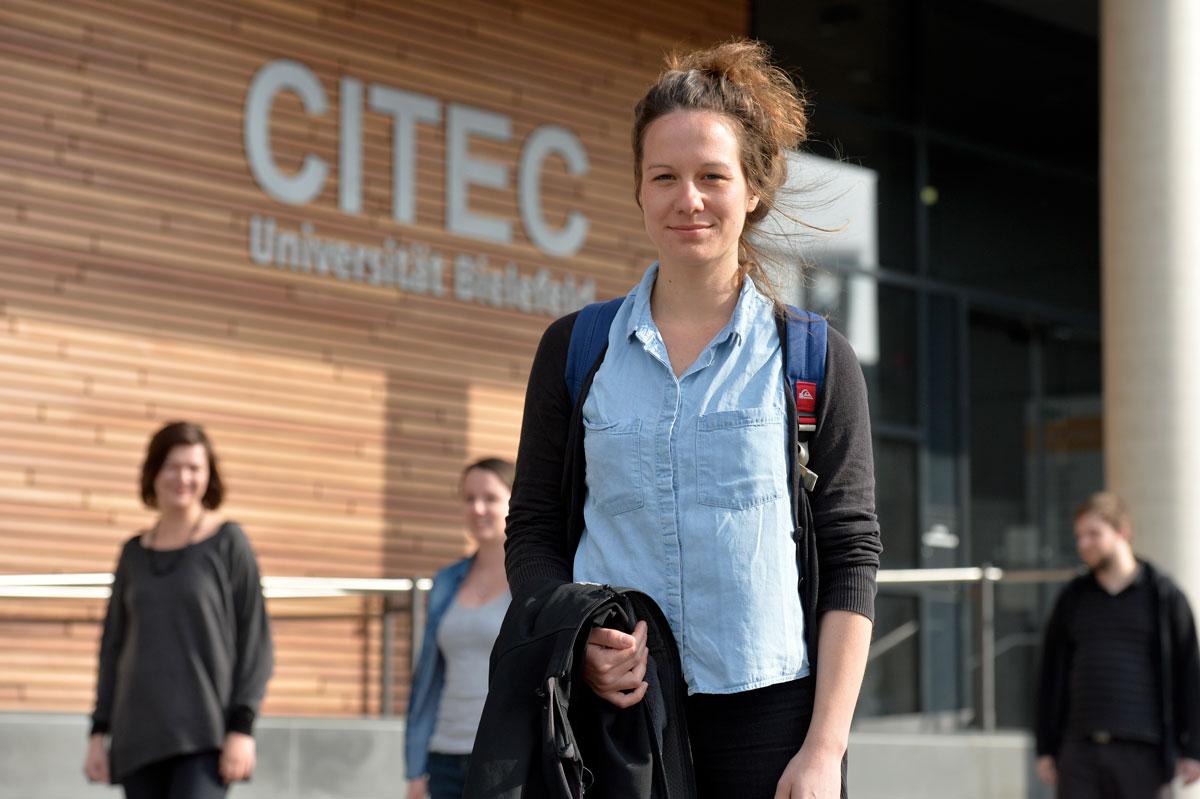 Eine Gruppe Student/innen in Bewegung vor einem Universitätsgebäude