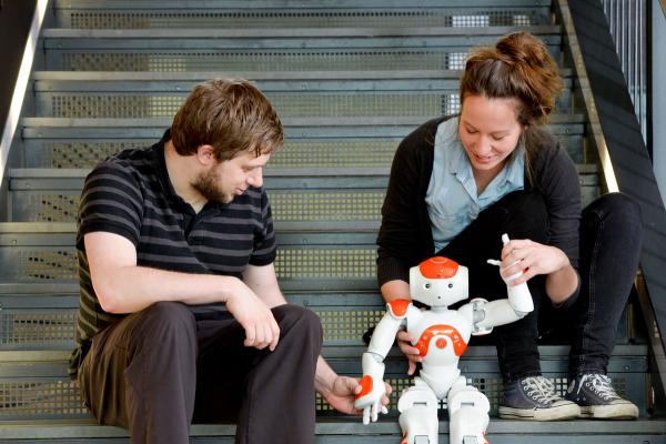 Ein Mann und eine Frau sitzen auf einer Treppe und betrachten einen Roboter