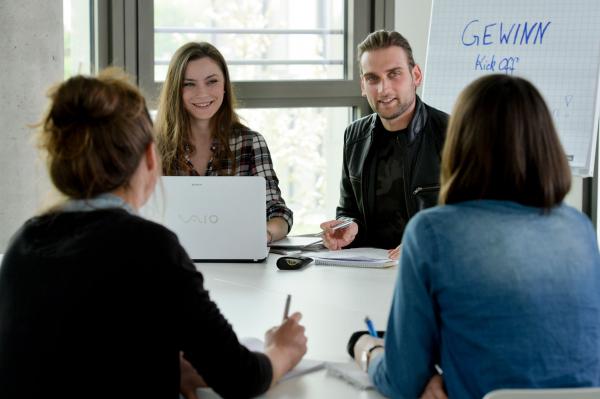 Drei Studentinnen und Studenten sitzen lernend an einem Tisch und sind miteinander im Gespräch